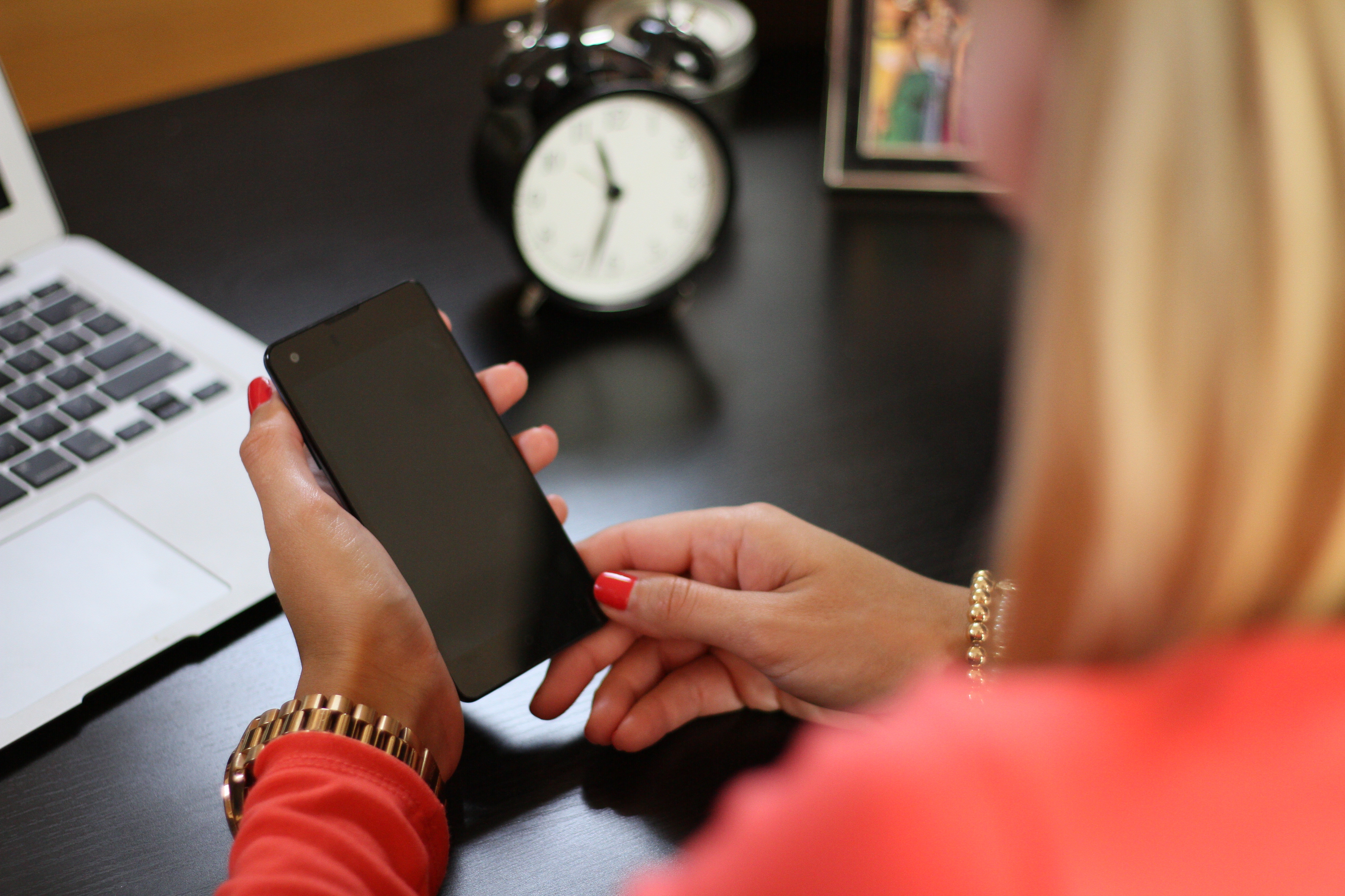 Picture of a woman using a phone in front of a laptop and a clock